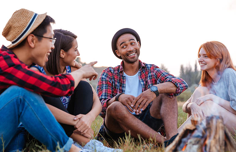 group of smiling young people sitting and talking near campfire