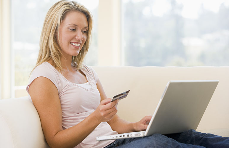 Woman in living room using laptop and holding credit card online shopping