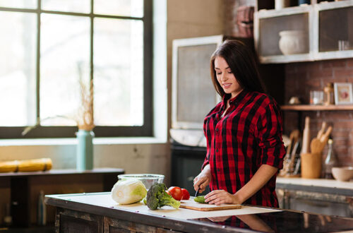 Pretty Woman in red shirt cooking in kitchen