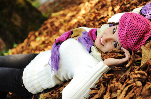 woman laying on autumn ground and leaves